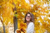 Young smiling girl-student in glasses close up against yellow au — Stock Photo