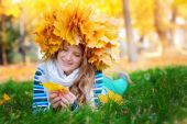 Young woman sitting on gold autumn leaves, top view  — Stock Photo