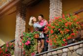 Couple in love on the balcony of red flowers — Stock Photo