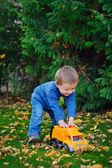 Joyful baby boy in autumn park playing machine — Stockfoto