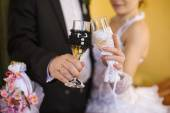 Decorated wedding glasses in the hands of the bride and groom — Stock Photo