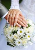 Hands of the groom and the bride with wedding rings and a weddin — Stock Photo