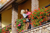 Loving couple on a balcony with flowers — Stock Photo