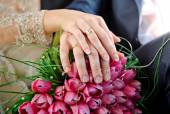 Hands with rings bride and groom on the wedding bouquet of pink — Stock Photo