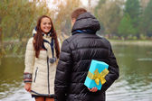 Back of a Japanese woman trying to pass a Christmas gift to man  — Stock Photo