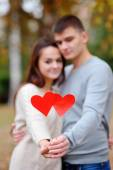 Hearts in the hands of a guy and a girl in focus against a backg — Stock Photo