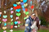 Couple kissing in the park, decoration background of hearts of p — Stock Photo