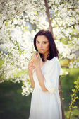 Beautiful brunette in the spring in a flowery park — Stok fotoğraf