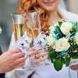 Two wedding glasses with champagne in hands of bride and groom — Stock Photo #57775123