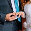 Groom dresses bride wedding ring on the finger — Stock Photo #57775139