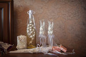 Wedding glasses and a bottle decorated with white flowers — Stock Photo