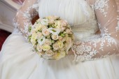Beautiful wedding bouquet in hands of the bride with roses — Stock Photo