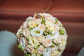 Wedding rings on a bouquet of cream roses — Foto Stock