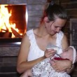 Mother feeds her baby with a bottle near a fireplace — Stock Video #58393877