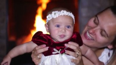 Mom plays with her daughter near a fireplace — Vidéo