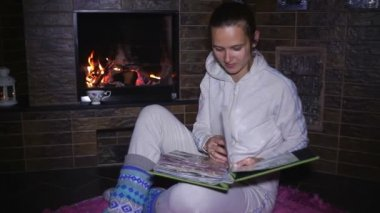 Beautiful girl sitting near the fireplace and watching photo album — Stock Video