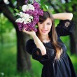 Beautiful girl in spring with a bouquet of lilacs — Stock Photo #58462333
