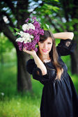 Beautiful girl in spring with a bouquet of lilacs — Stock Photo