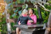 Lovers kissing on a bench in the park — Stockfoto