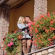 Man and woman on the balcony and a lot of red flowers — Stock Photo #59169765