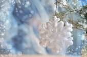 Christmas decorations - toys white snowflakes on silver material — Stock Photo