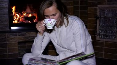 Girl with cup of tea sitting near the fireplace — Stockvideo