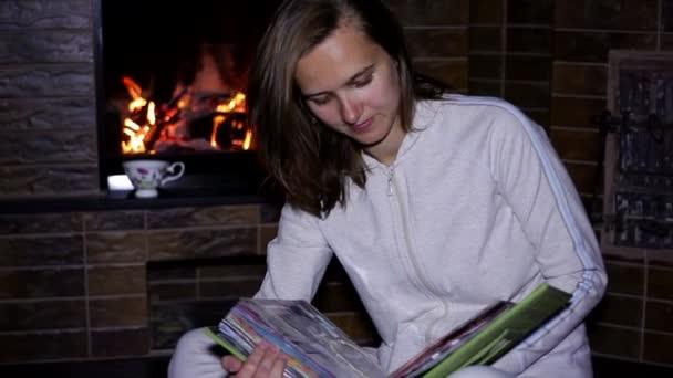 Chica sentada cerca de la chimenea y hojeando un álbum — Vídeo de stock
