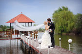 Bride and groom kissing on a bridge — Stock Photo