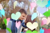 Couple in love on Valentine's Day in the Park with hearts — Stock Photo