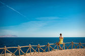 Woman looks at the sea and the island of Tiran, Egypt — Stock Photo