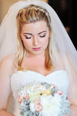 Portrait of a beautiful blonde bride with a bouquet — Stock Photo