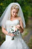 Beautiful blonde bride with bouquet in park — Stock Photo