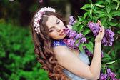 Mooie vrouw in een park van de lente ruiken de seringen — Stockfoto