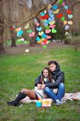 Lovers walking in the park in spring decor paper hearts — Stock Photo