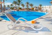 Chaise longue on the background of the pool at the hotel — Stock Photo