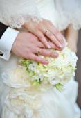 新娘和新郎带上婚礼花束的戒指的手. — 图库照片