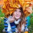 Beautiful woman in the autumn wreath of maple yellow leaves — Stock Photo #62199135