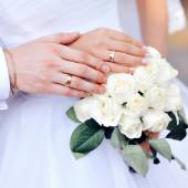 Hands of the bride and groom with wedding rings on bouquet — Stock Photo
