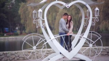 Loving couple standing in the gazebo in the form of heart in the park — Stock Video
