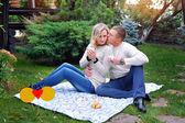 Liefde paar zittend op een bed in het park met een picknick — Stockfoto