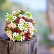 Beautiful wedding bouquet with red flowers lying on a tree stump — Stock Photo #63088313