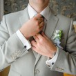 Man in a suit straightens his tie with cufflinks on their sleeve — Stock Photo #63326933