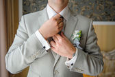 Man in a suit straightens his tie with cufflinks on their sleeve — Stock Photo