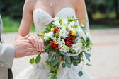 Hands with rings bride and groom with wedding bouquet — Stockfoto