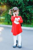 Little girl in big shoes talking on the phone — Stock Photo