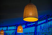 Beautiful wicker lamp on a blue background — Stock Photo