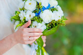 Bride with a ring holding a wedding bouquet of blue hydrangea fl — Stock Photo