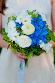 Bride holding a wedding bouquet of blue hydrangea flowers — Stock Photo
