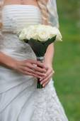 Bride is holding a wedding bouquet of white — Stock Photo
