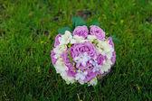 Ramo de rosas color púrpuras en la hierba — Foto de Stock
